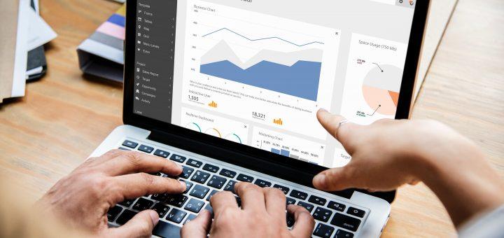 Hände zeigen auf Graphen am Laptop
